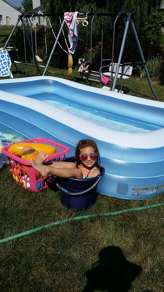 An entire pool and she sits in the foot bucket!